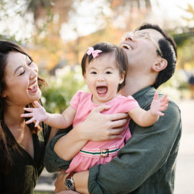 Mom and dad laugh while baby daughter opens her mouth wide at McKinley Park Rose Garden Sacramento