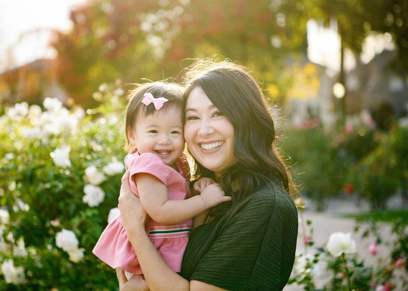 Mom smiling and hugging toddler daughter close at McKinley Park Rose Garden Sacramento