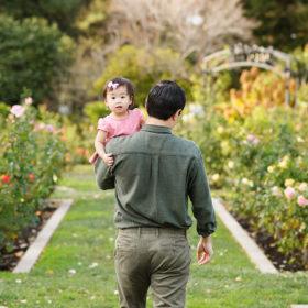 Dad holding toddler daughter as she looks at camera at McKinley Park Rose Garden Sacramento