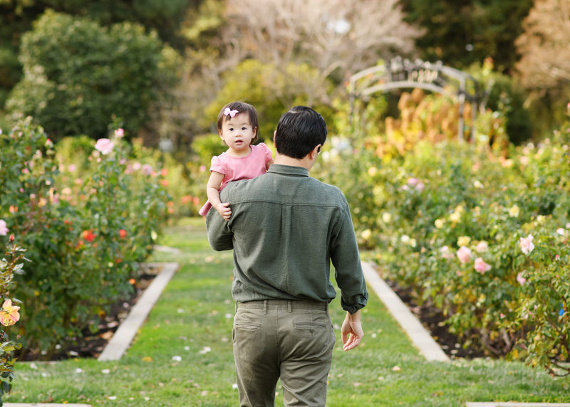 Dad holding toddler daughter as she looks at camera at McKinley Park Rose Garden Sacramento