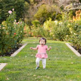 Toddler girl running through grass at the Rose Garden in McKinley Park Sacramento