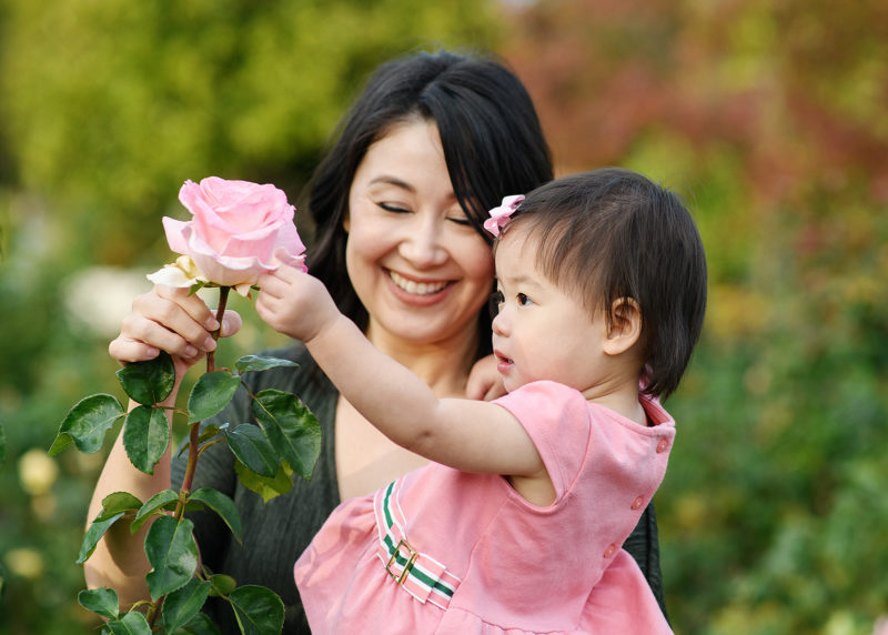 Toddler daughter touching pink rose as mom holds her and smiles at McKinley Park Rose Garden Sacramento
