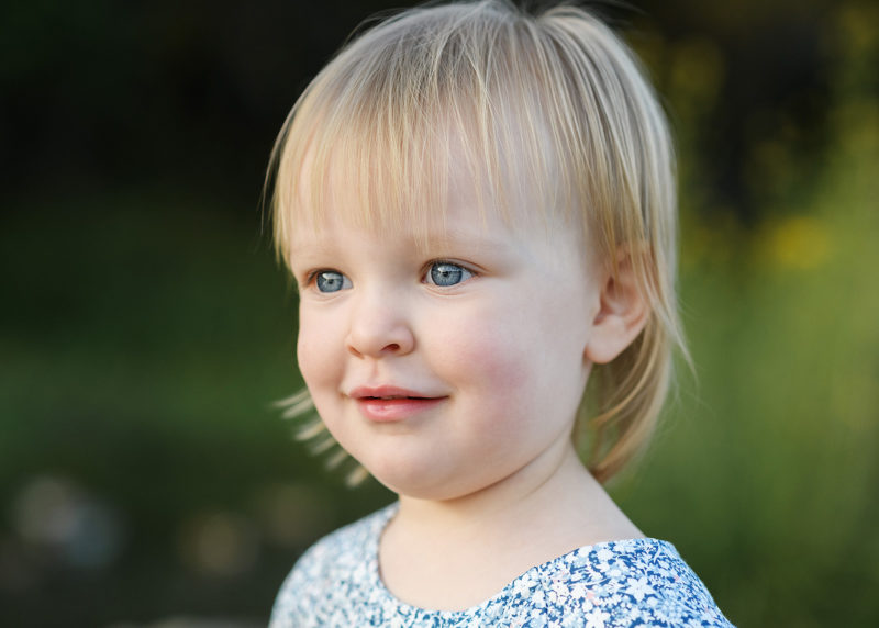 Blonde toddler girl with blue eyes close up outdoors in Fair Oaks