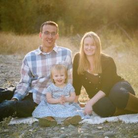Family photo during golden hour light in Fair Oaks on picnic blanket and dry grass