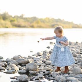 Toddler girl skipping rocks by lake in Fair Oaks