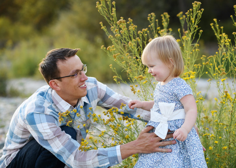 Dad holding toddler daughter by yellow wildflowers and smiling in Fair Oaks