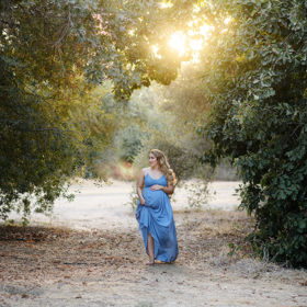 Pregnant woman wearing light blue dress walking in between trees in Davis