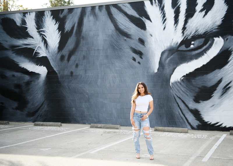 High school senior girl standing in front of tiger mural in downtown Sacramento