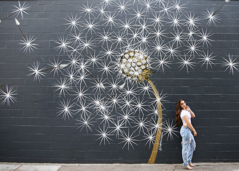 Teen girl posing in front of dandelion mural in downtown Sacramento