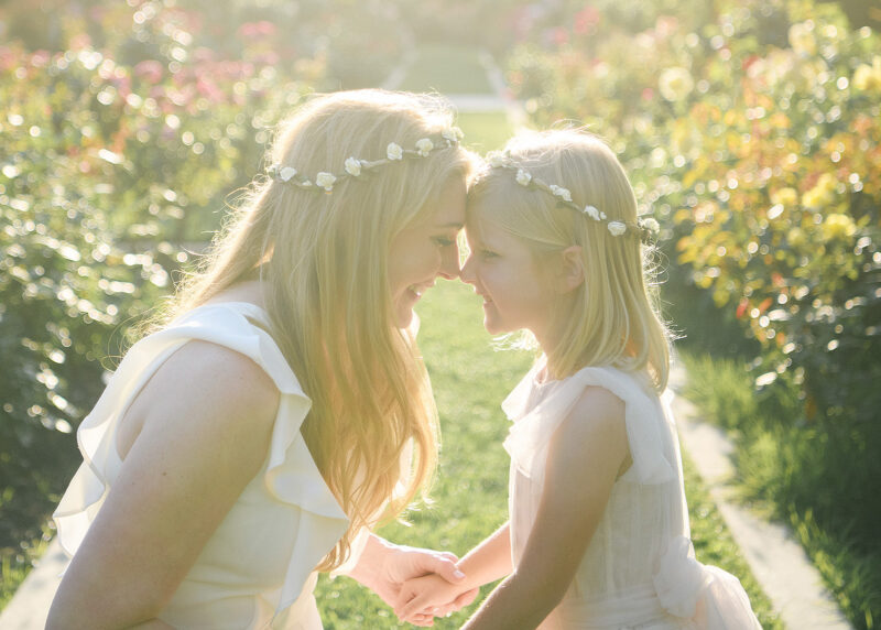 Mom and daughter touching foreheads and holding hands wearing flower crowns against sunset light McKinley Park