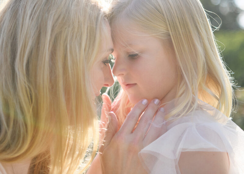 Mom pressing forehead against daughter and touching her face during sunset at McKinley Park Rose Garden