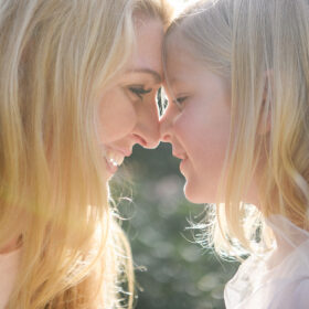 Mom nose to nose with daughter in sunlight in McKinley Park Sacramento