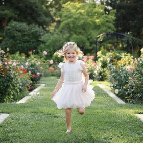 Little girl in white dress runs on grass at McKinley Park Rose Garden