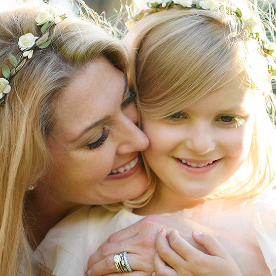 Mom and daughter hugging and smiling while wearing flower crowns