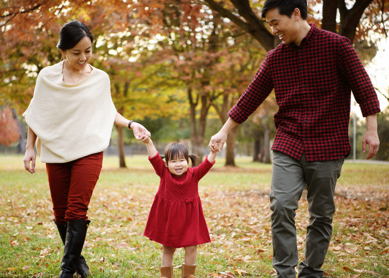 Mom and dad holding toddler girl's hands while she walks on fall leaves in Rancho Cordova Sacramento