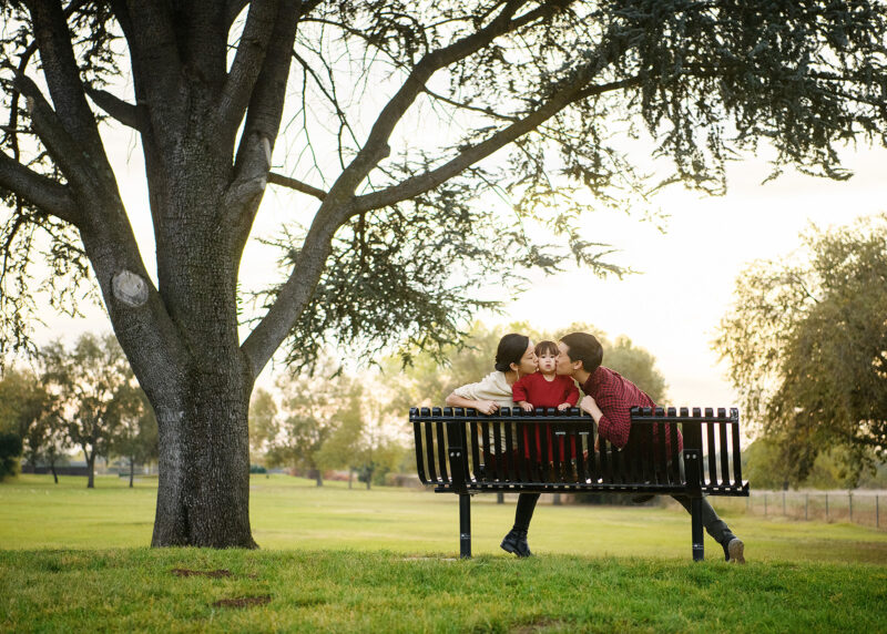 Mom and dad kissing toddler girl on cheek while sitting on a park bench under a tree Rancho Cordova Sacramento