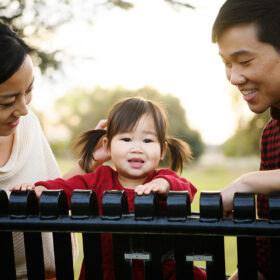 Mom and dad looking ad toddler daughter as she looks directly into camera while sitting on park bench in Rancho Cordova Sacramento