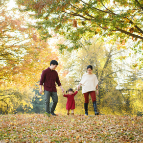 Mom and dad holding toddler girl's hand as they walk through fall leaves