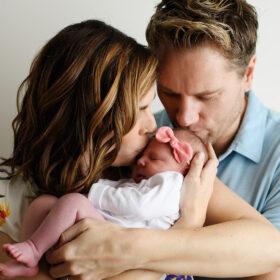 Mom and dad kissing newborn baby girl on head in Sacramento studio