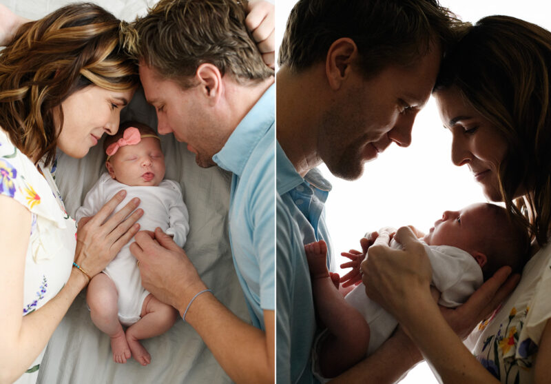 Mom and dad looking lovingly at newborn daughter while sleeping in studio