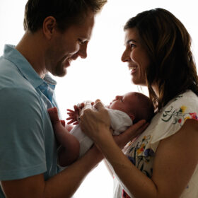 Mom and dad against the light soft silhouette looking at each other while holding newborn baby daughter