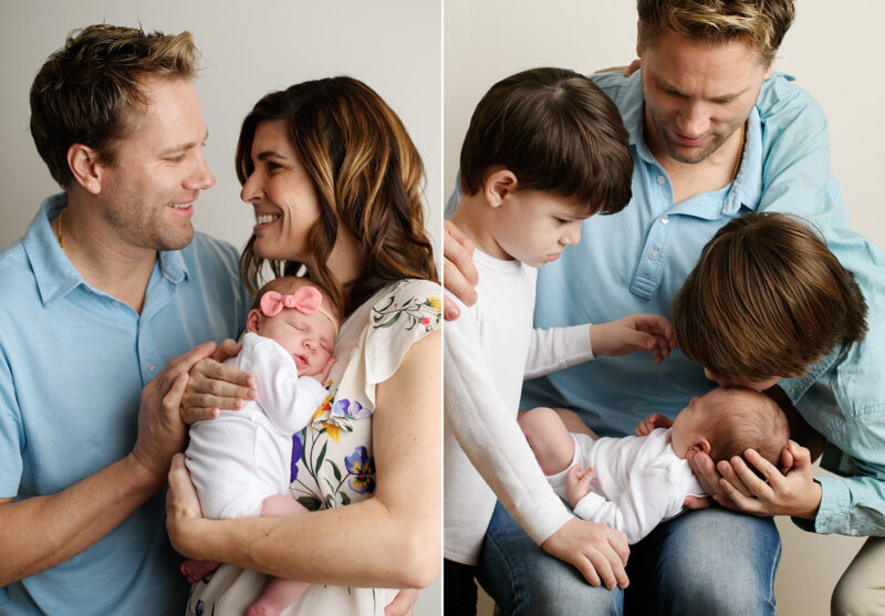 Big brother kissing newborn baby sister as dad holds her in studio
