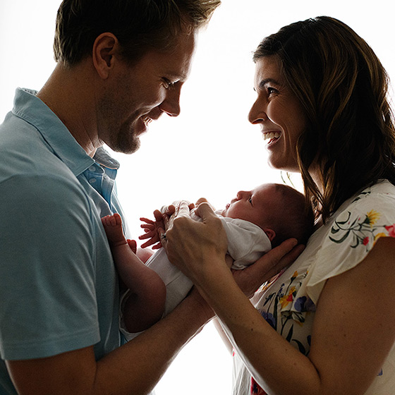 Mom and dad soft silhouette holding newborn baby girl and smiling in Sacramento studio