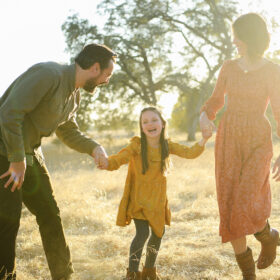 Mom and dad holding hands with daughter and laughing on dry grass in Folsom