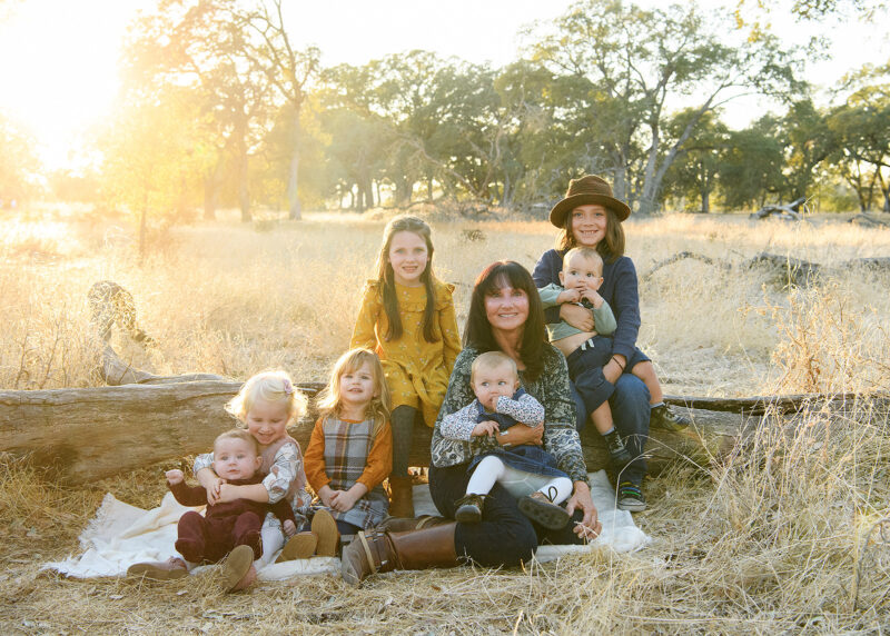 Grandma group picture with grandchildren sitting on dry grass and a log in Folsom