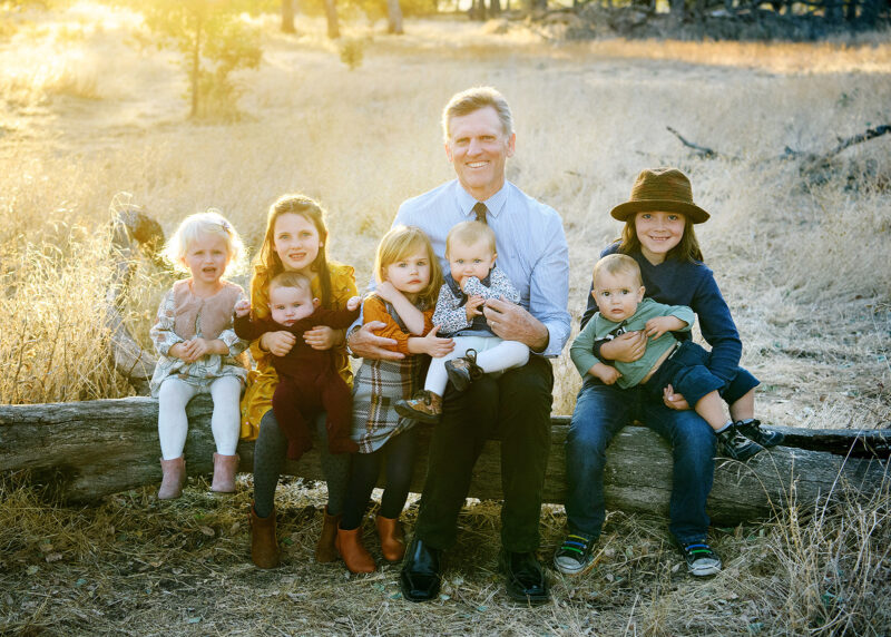 Grandpa sitting on a log with all the grandchildren in Folsom