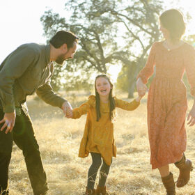 Daughter laughing while holding hands with mom and dad in Folsom dry grass during sunset