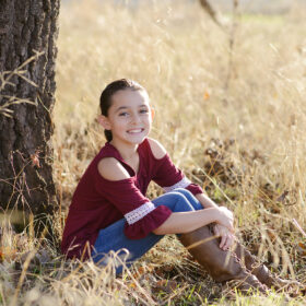 Girl wearing red top and boots sitting on dry grass under a tree in Cameron Park
