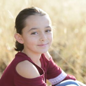 Girl smiling directly at camera close up with dry grass background in Cameron Park