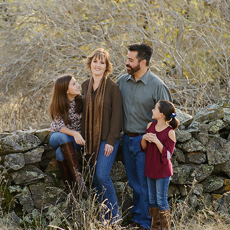 Family sitting on stone wall with background of dry trees in Cameron Park during autumn
