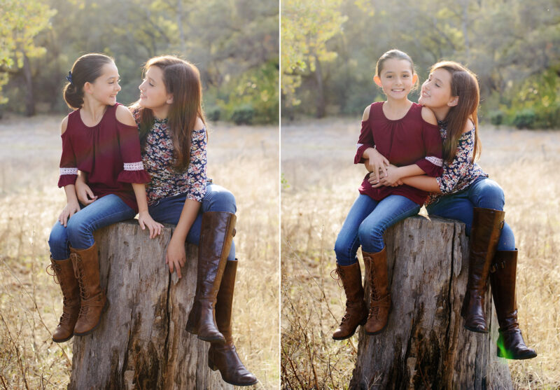 Sisters hugging and looking at each other while sitting on tree stump in Cameron Park