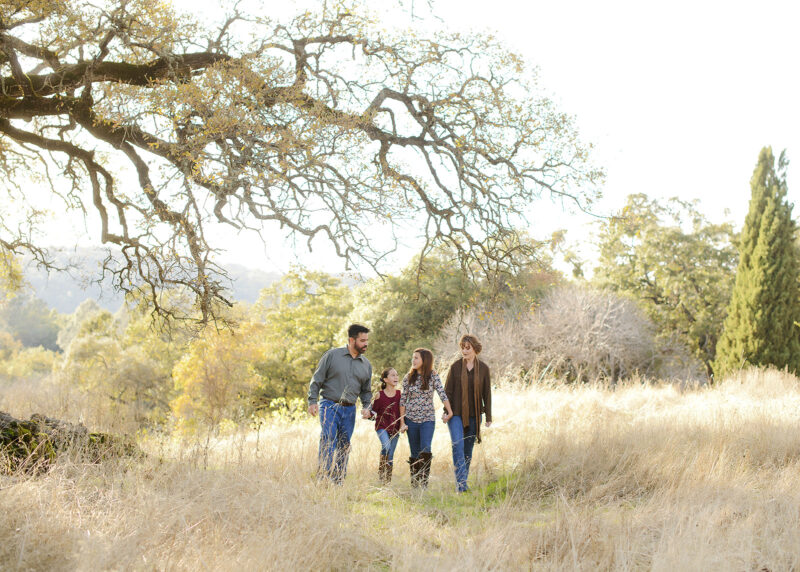 Family walking through dry grass under a large tree in Cameron Park