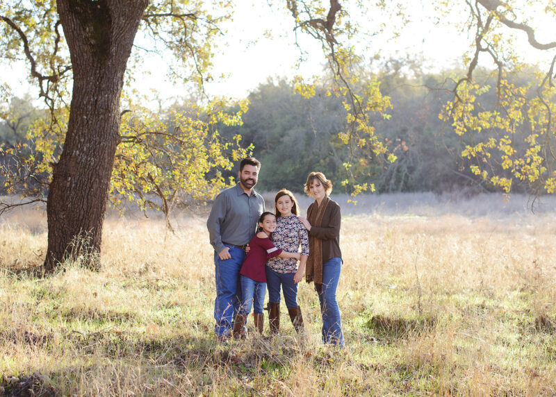 Family picture under a large tree while standing on dry grass in Cameron Park