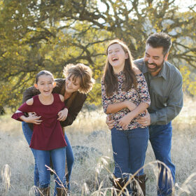 Family laughing and hugging on dry yellow grass in Cameron Park Sacramento