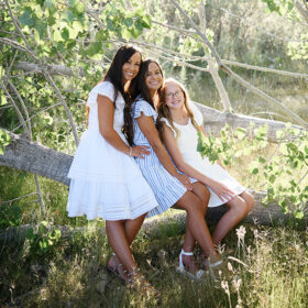 Mom and daughters sitting on tree trunk surrounded by leaves in Folsom Lake