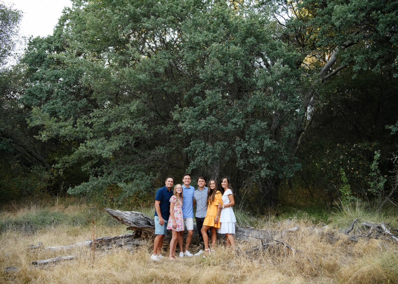 Group family picture in front of fallen log and dry grass with tall trees in background Folsom Lake