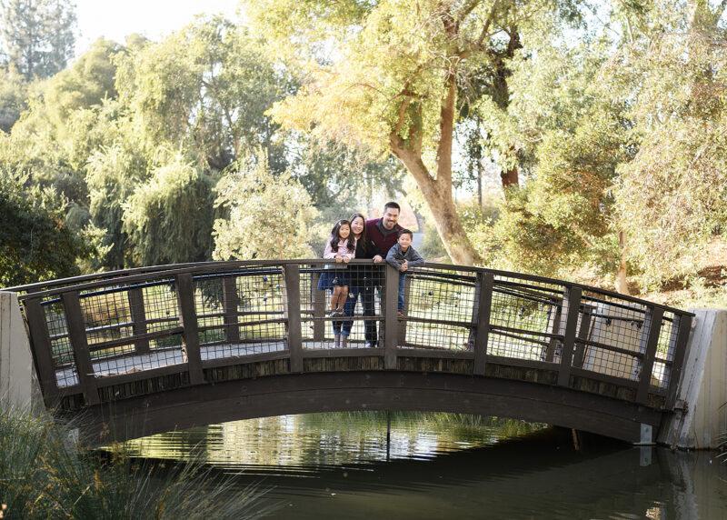 Family smiling on walking bridge in Davis