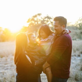 Mom and dad holding son and daughter and smiling directly in golden sunset light