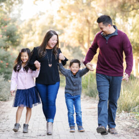 Mom and dad holding son's hand with daughter walking in Davis