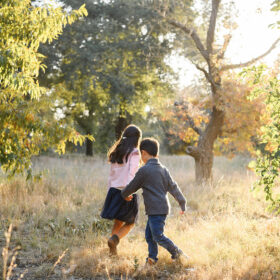 Brother and sister run through the dry grass in between trees in Davis