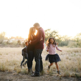 Mom and dad hug each other while son and daughter run around them in Davis