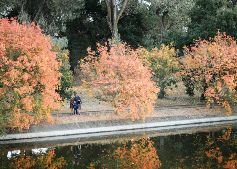 Extended long shot of fall foliage with reflection on water with family in Davis