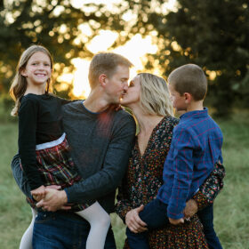 Mom and dad kiss while holding son and daughter with sunset in background in Sacramento