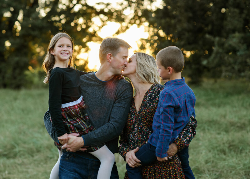 Mom and dad kiss while holding son and daughter with sunset in background in Davis