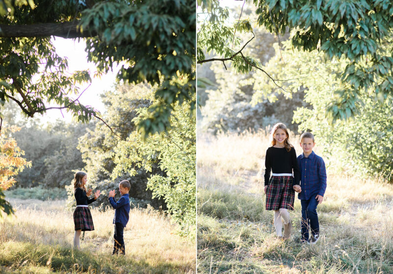 Brother and sister playing games while framed with tree branches in dry grass in Davis