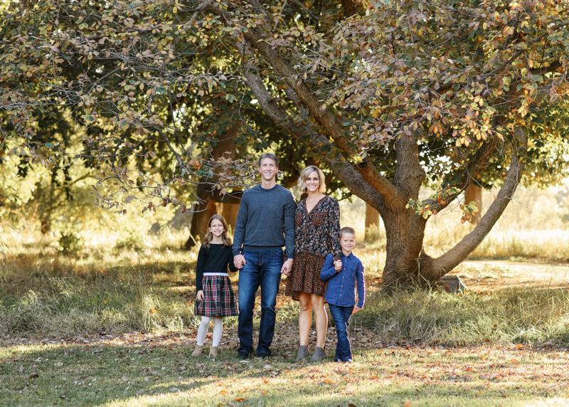Fall family photo underneath large tree in Sacramento park